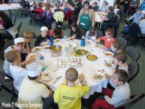 Mirela am Tisch mit ihren KochschülerInnen beim Kinderkochkurs im FEZ (Foto © AG F+M)